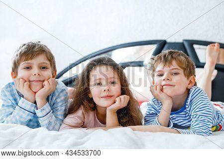 Three Happy Kids In Pajamas Celebrating Pajama Party. Preschool And School Boys And Girl In Nightwea