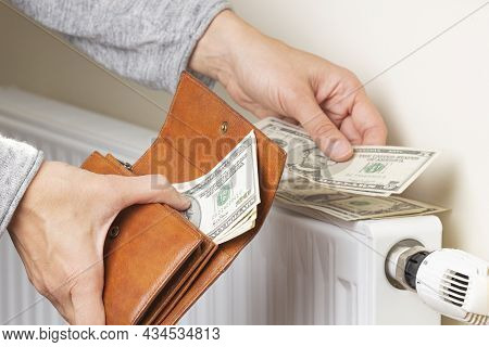 Womans Hand Takes Us Dollars Banknotes From Wallet And Places On Heating Radiator Battery With Tempe