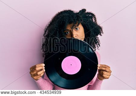 African american woman with afro hair holding vinyl disc in shock face, looking skeptical and sarcastic, surprised with open mouth