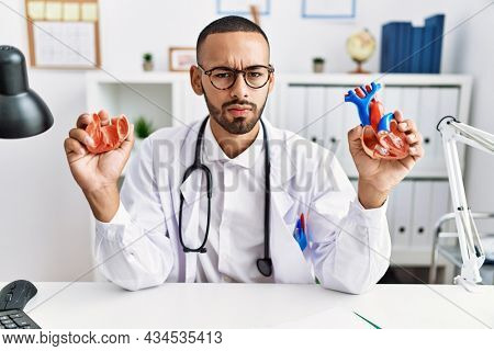 African american doctor man holding anatomical heart at the clinic skeptic and nervous, frowning upset because of problem. negative person.