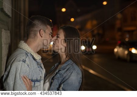 Portrait Of Kissing Young Couple On Night City Background. Beautiful Young Couple In Love. Romantic