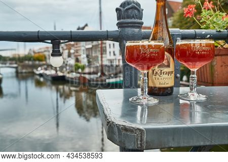 ROTTERDAM, THE NETHERLANDS - CIRCA2019: La Trappe Dutch Trappist abbey beer poured into glasses on an outdoor terrace in Delfshaven, pleasant view over the canals, Cafe de Oude Sluis terrace