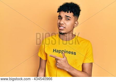 Young african american man wearing t shirt with happiness word message pointing aside worried and nervous with forefinger, concerned and surprised expression