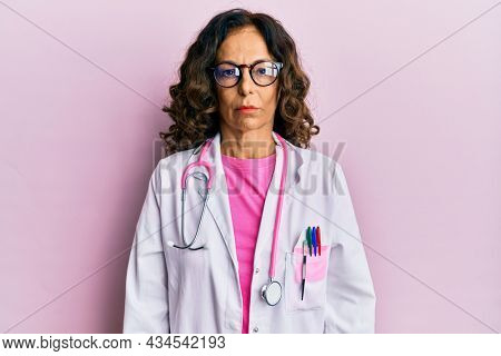 Middle age hispanic woman wearing doctor uniform and glasses depressed and worry for distress, crying angry and afraid. sad expression.