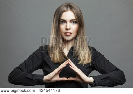 Beautiful Woman Folded Her Arms In The Shape Of A Pyramid. Spectacular Smiling Blonde In A Black Shi