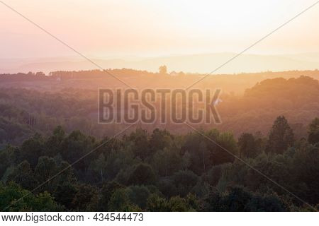 Idyllic Countryside Landscape With Forest Layers And Orange Glowing Haze On The Horizon At Evening
