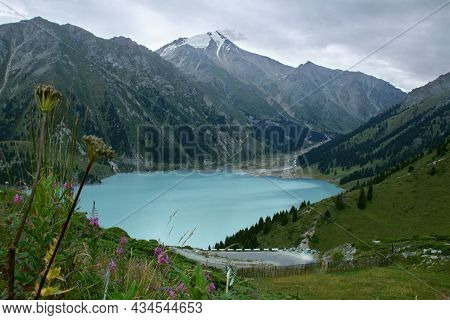 Alpine Blue Lake, The Sky In Clouds, A Lake Surrounded By Mountains, Trees, Grass And Flowers Grow O