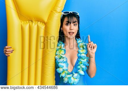 Young brunette woman with bangs wearing swimsuit and holding summer float surprised with an idea or question pointing finger with happy face, number one