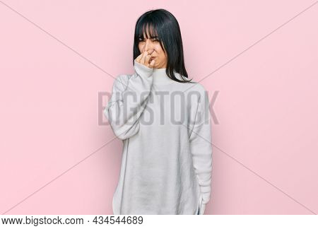 Young brunette woman with bangs wearing casual turtleneck sweater smelling something stinky and disgusting, intolerable smell, holding breath with fingers on nose. bad smell