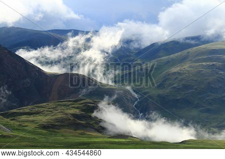 In A High-mountainous Green Gorge Among The Mountain Slopes, A River Flows Far, In The Gorge Low Whi