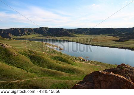In A Steppe Valley With Low Mountains In The Distance, A Wide Calm River Ili Flows, Surrounded By Gr