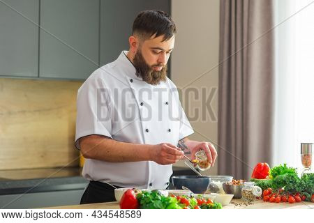 Young prepares a poke bowl in a modern kitchen. The man prepares food at home. Cooking healthy and tasty food
