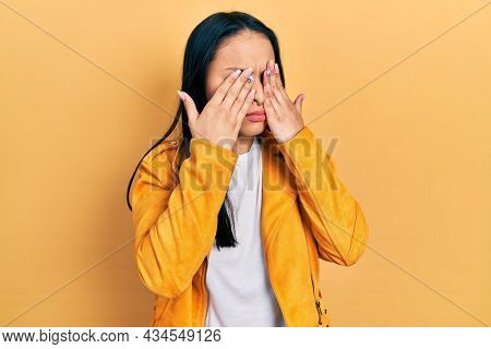 Beautiful hispanic woman with nose piercing wearing yellow leather jacket rubbing eyes for fatigue and headache, sleepy and tired expression. vision problem