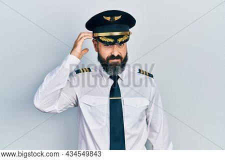 Young hispanic man wearing airplane pilot uniform confuse and wonder about question. uncertain with doubt, thinking with hand on head. pensive concept.
