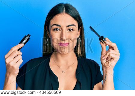Young hispanic woman holding eyelash mascara puffing cheeks with funny face. mouth inflated with air, catching air.