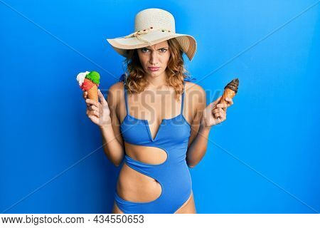 Young caucasian woman wearing summer style holding ice cream skeptic and nervous, frowning upset because of problem. negative person.
