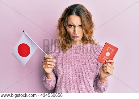Young caucasian woman holding japan flag and passport skeptic and nervous, frowning upset because of problem. negative person.