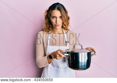 Young caucasian woman wearing apron holding cooking pot skeptic and nervous, frowning upset because of problem. negative person.