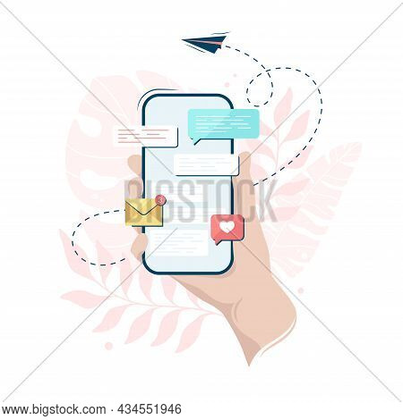 Hand Holding A Smartphone With A Messenger On Its Screen, On A Leaves Background