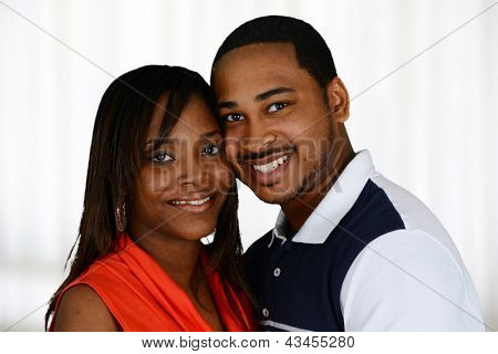Young happy couple standing together inside their home