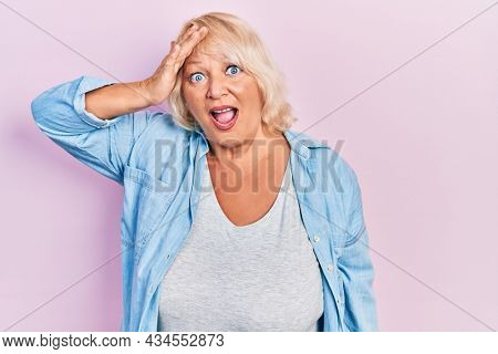 Middle age blonde woman wearing casual clothes surprised with hand on head for mistake, remember error. forgot, bad memory concept.