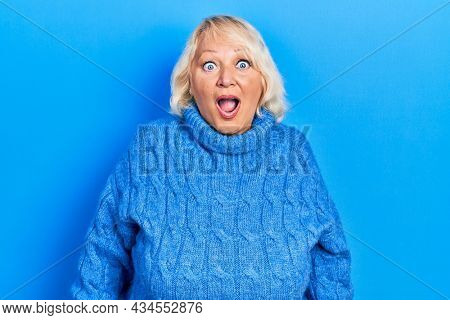Middle age blonde woman wearing casual clothes afraid and shocked with surprise and amazed expression, fear and excited face.