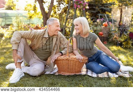 Lovely Senior Couple Having Picnic Outdoors, Sitting On Blanket And Smiling To Each Other, Enjoying