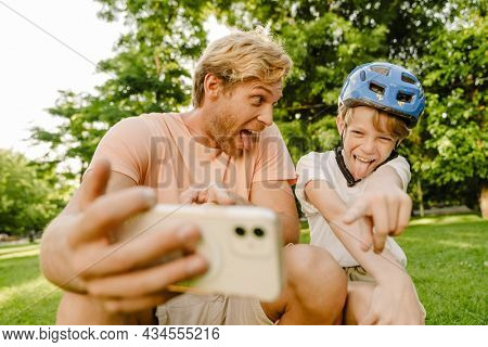 Ginger man and his son grimacing while taking selfie on cellphone in green park