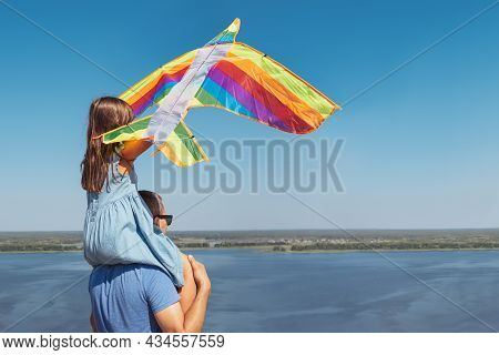 A Little Girl Sits On Her Fathers Shoulders And Plays With A Colorful Kite.