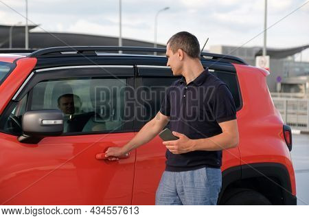 Man Using Smartphone, Holding In Hand Near The Car About In The Parking Lot