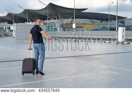 Young Man With Luggage Locking Car With Remote Key Alarm Outdoors