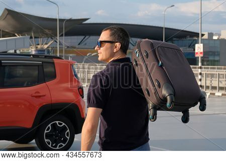 Young Man With A Suitcase In His Hand Near The Car In The Parking Lot On A Sunny Day
