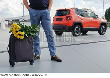 Cropped View Of Man With Luggage And Flowers In Car Park Outside