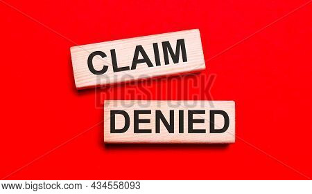On A Bright Red Background, There Are Two Light Wooden Blocks With The Text Claim Denied