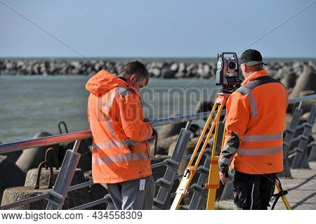 Klaipeda, Lithuania - September 25: Surveyor Workers With Geodesy Equipment Device At September 25,