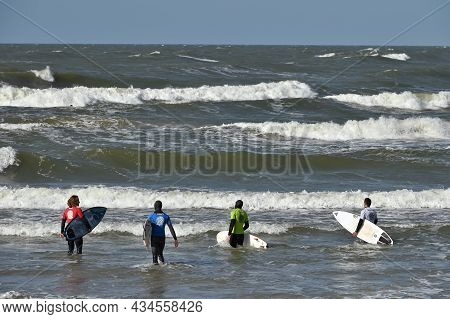 Klaipeda, Lithuania - September 25: A Surfers In Wetsuits Preparing For Ride On The Waves At The Bea