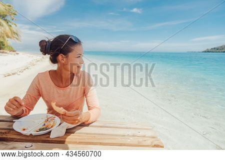French Polynesia Beach picnic motu tour on Huahine, Tahiti, French Polynesia. Happy tourist woman eating at table in ocean water feet in sand for summer lunch. Travel lifestyle