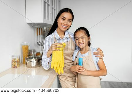 Pretty Asian Girl Helping Mother With Household, Standing In Kitchen And Smiling, Enjoying Learning