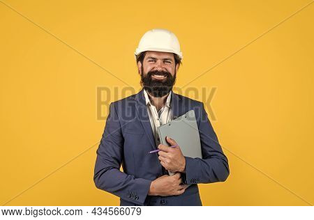 Architecture And Building. Male Builder Wearing Formal Suit And Helmet For Protection. Working On Co