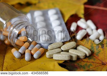 Pills On Yellow Maple Leaves, Bottle Of Capsules And Blister Packs Of Tablets. Concept Of Nutrition