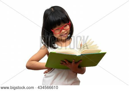 Happy Asian Little Preschool Girl Wearing Red Glasses Holding And Read A Green Book On White Isolate