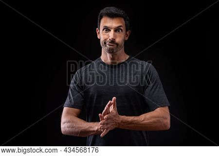 The Athlete Man, Grimaces, Builds Facial Expressions, On A Black Background. Extreme Human Emotions.