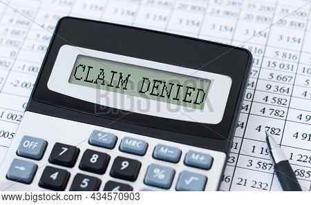 A Calculator Labeled Claim Denied Is On The Table Near The Report. Financial Concept