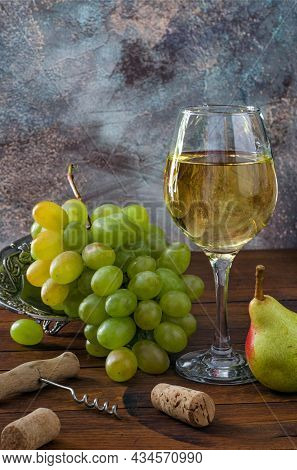 Glass With White Wine, Bunch Of Grapes And Corkscrew On Wooden Table. Сlose-up.