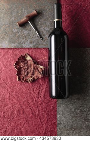 Bottle Of Red Wine With A Corkscrew On Vintage Background. Top View With Copy Space.