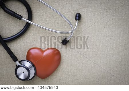 Black Stethoscope With Red Heart Of Doctor For Check Up On Beige Background. Stethoscope Equipment O