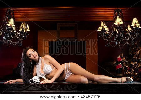 Fashion model wears white clothes with retro headphones lying on bar