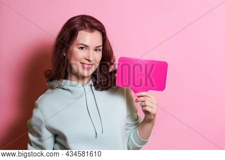 Beautiful Woman In A Hoodie Holds A Tablet In Her Hands And Smiles. Social Media Communication Conce