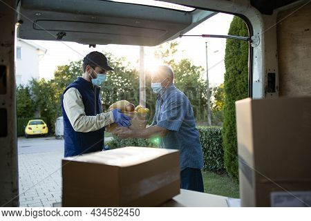 Senior Man Accepting Food Delivery From Deliveryman During Covid19 Pandemic Or Lockdown.