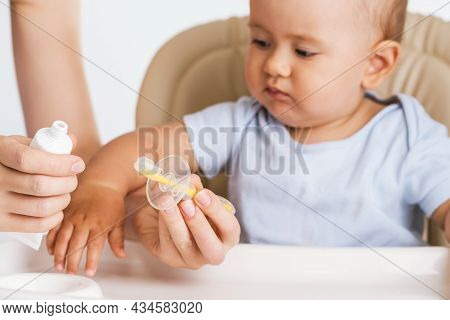 The Concept Of Brushing Teeth In A Newborn Baby. A Mother's Hand Puts Paste On A Toothbrush For A Ne